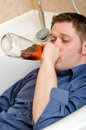 Drunk man drink alcohol lying in bath Royalty Free Stock Photo