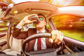 Drunk man driving a car vehicle in suit and sunglasses on road in the Royalty Free Stock Image