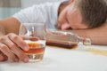 Drunk man with a glass of liquor young sleeping on table Stock Photography