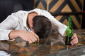 Drunk man lying on a counter with bottle of beer Royalty Free Stock Photo