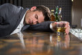 Drunk man lying on a counter with glass of whisky Royalty Free Stock Photo