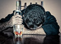 Drunk man sleeping with his head on a table depressed glass and bottle Royalty Free Stock Images