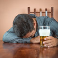 Drunk man sleeping on a table holding glass of beer his hand Stock Photography