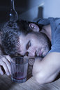 Drunk and passed out bearded caucasian man sleeps with head lying on arms over table next to empty glass bottle of alcohol in Stock Photos