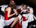 Drunk santa claus lying on sofa, female nurse woman in carnival costume, tries to wake him up Royalty Free Stock Photo