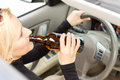 Drunk woman imbibing as she drives high angle view of a driver sitting behind her steering wheel from a bottle of alcohol Royalty Free Stock Image
