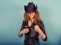 Drunk woman raising her fist a wearing a cowboy hat is he and is looking aggressive Royalty Free Stock Photo