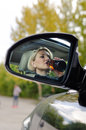 Drunk woman about to cause an accident reflection in the side rear view mirror of a driver drinking from upended bottle and Royalty Free Stock Photos
