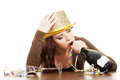 Drunk young woman sitting with empty champagne bottle isolated on white Royalty Free Stock Photos