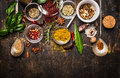 Dry colorful spices in spoons and bowls with fresh seasoning on dark rustic wooden background top view border Royalty Free Stock Image