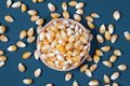 The dry corn kernels in a wooden bowl are placed on a green board with dry corn kernels spread on  board Royalty Free Stock Photo