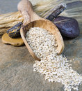 Dry oat cereal in wooden spoon on stone setting vertical photo of rolled oats with rocks and wheat stalks natural Royalty Free Stock Photography