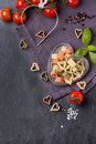 Dry pasta as hearts top view on colorful heart shape with fresh tomatoes and basil served on dark gray background Royalty Free Stock Photography