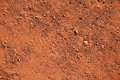 Dry red clay texture of with stones close up Stock Images