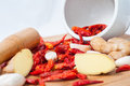 Dry red pepper ginger and garlic on chopping board with a mortar pestle Stock Photos