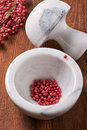 Dry rose pepper in white marble mortar next pestle Royalty Free Stock Photo