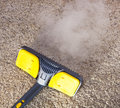 Dry steam cleaner in action using to sanitize floor carpet Royalty Free Stock Photo
