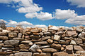Dry stone wall against blue sky clouds Stock Photos