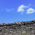 Dry stone wall a with blue sky Royalty Free Stock Image