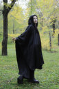 Dryad follow me black hooded woman in the autumn forest turning back at you while walking as if beckoning Royalty Free Stock Photo