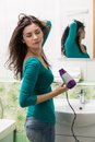 Drying hair a young woman in front of a bathroom mirror vertical shot Royalty Free Stock Images