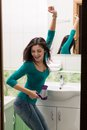 Drying hair a young woman in front of a bathroom mirror vertical shot Stock Images
