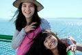 Duas meninas felizes que sorriem na plataforma da balsa com o oceano no fundo Imagens de Stock