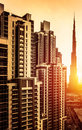 Dubai downtown in sunset uae beautiful tall buildings bright yellow sul light burj khalifa business centre luxury travel and Stock Images