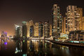 Dubai marina high rise apartments against the dark night calm water of the artificial canal reflects skyline Stock Images