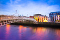 Dublin ireland at dusk with waterfront and historic ha penny bridge Stock Photos