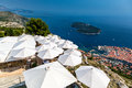 Dubrovnik Croatia. Top view over restaurant with sun umbrellas and the old town below. Royalty Free Stock Photo