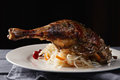 Duck confit closeup served with sauerkraut on a wooden tabletop in darkness Royalty Free Stock Images