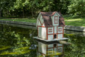 Duck house on a pond with background of trees Royalty Free Stock Images