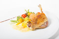 Duck leg confit served with vegetables on a white plate Stock Images