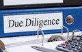 Due diligence text on a white label fixed to a blue folder place on a desk with another binder and calculator concept of checking Royalty Free Stock Images