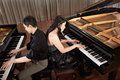 Duet with pianos two people a couple playing musical performance two grand Stock Photo