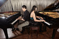 Duet with pianos two people a couple playing musical performance two grand Stock Image