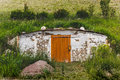 Dugout with a wooden door in a hill with green grass in a rural farmer`s locality