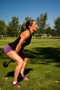 Dumbbell swing woman doing swings in a park Royalty Free Stock Photos