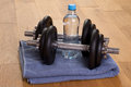 Dumbbells and bottle of water in a gym on wooden floor Royalty Free Stock Images