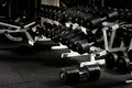 Dumbbells many black in dark weight room horizontal photo Stock Photography