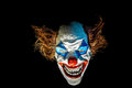 Dummy clown scary face isolated in black night scene Stock Photo