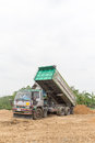 Dump truck dumps its load of rock and soil on land thailand Stock Photography
