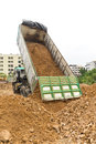 Dump truck dumps its load of rock and soil on land thailand Stock Image