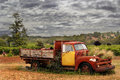 Dumped truck an old lies and rusting in a field as storm clouds threaten Stock Image