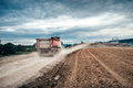 dumper trucks working on highway construction site, loading and unloading gravel and earth. heavy duty machinery activi Royalty Free Stock Photo