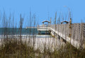 Dune grass and fishing pier a is visible through the in a gulf coast beach Stock Photography