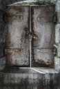 Dungeon door an old rustiong cast iron letting in chinks of sunlight Stock Photos
