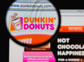Dunkin donuts photo of homepage on a monitor screen through a magnifying glass Royalty Free Stock Photo