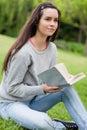 Durchdachte junge Frau, die ein Buch anhält Stockbilder